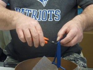 Gate Cutters as demonstrated by an operator trimming injectiion molded parts free from the gate